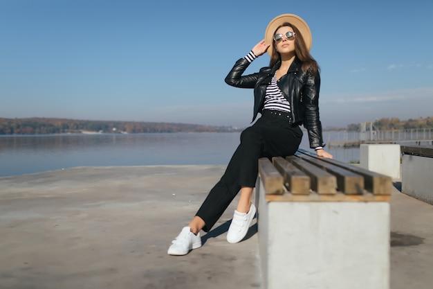 Jeune femme modèle fille posant en journée d'automne au bord du lac habillé en vêtements décontractés