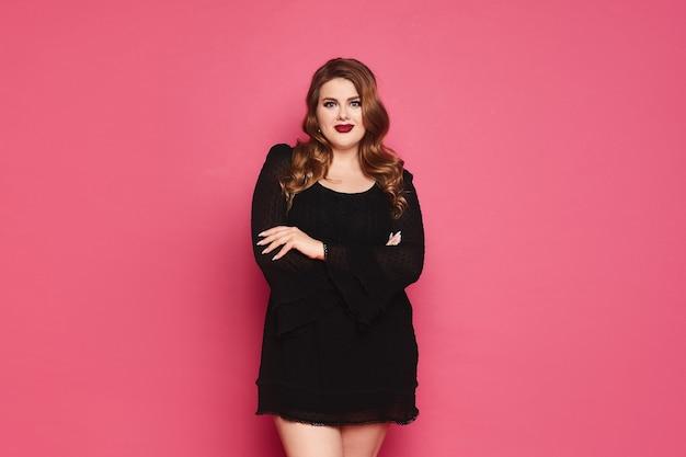 Jeune femme modèle de taille plus caucasienne en robe noire les mains jointes et posant sur un mur rose isolé avec espace de copie