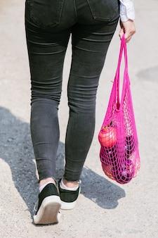 Une jeune femme moderne avec des achats. la fille porte des fruits et des légumes dans une ficelle écologique, un sac en filet réutilisable. fruits biologiques dans un sac en filet