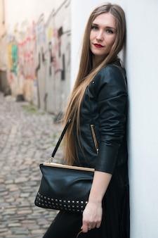 Jeune femme moderne à côté du mur blanc