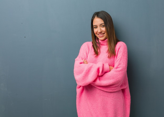 Jeune femme moderne croisant les bras, souriante et détendue