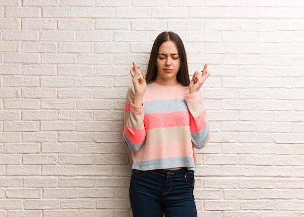 Jeune femme moderne croise les doigts pour avoir de la chance