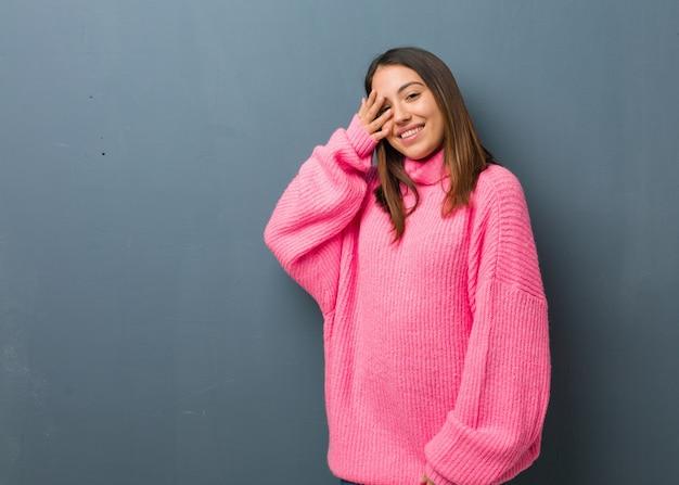 Jeune femme moderne embarrassée et riant en même temps