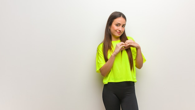 Jeune femme moderne faisant une forme de coeur avec les mains
