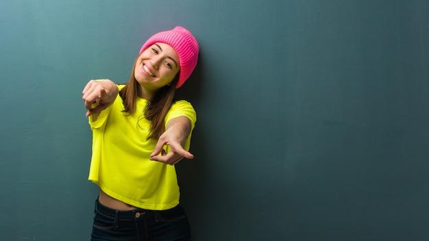 Jeune femme moderne gaie et souriante pointant vers l'avant