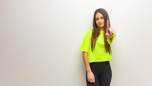 Jeune femme moderne montrant le numéro un