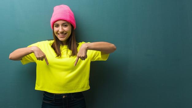 Jeune femme moderne pointant vers le bas avec les doigts