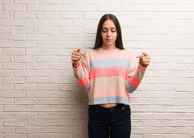 Jeune femme moderne pointant vers le bas