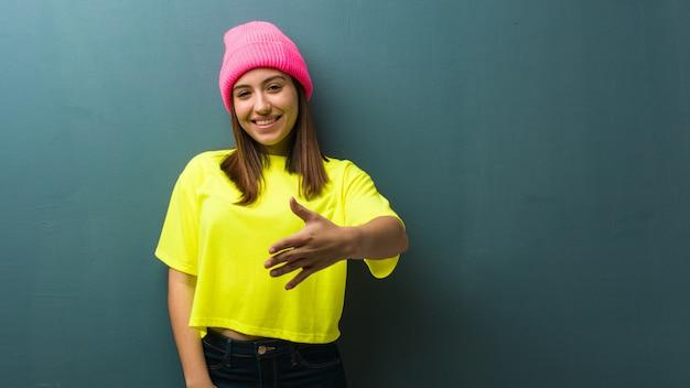 Jeune femme moderne tendre la main pour saluer quelqu'un
