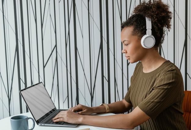 Jeune femme moderne travaillant à domicile sur son ordinateur portable