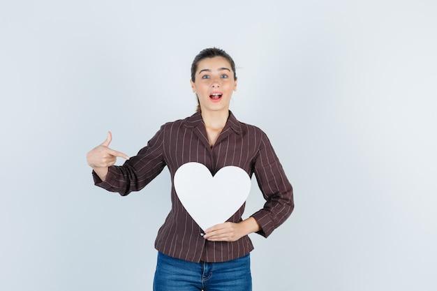 Jeune femme montrant une affiche en papier en chemise, un jean et l'air surpris, vue de face.
