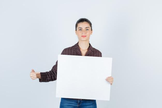 Jeune femme montrant une affiche en papier en chemise, vue de face de jeans.