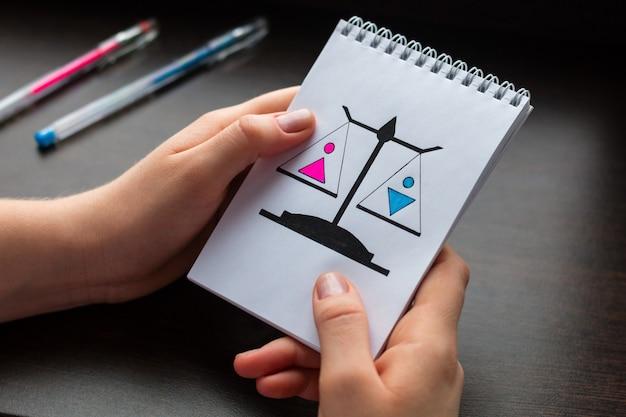 Jeune femme montrant un bloc-notes avec le concept d'égalité des sexes