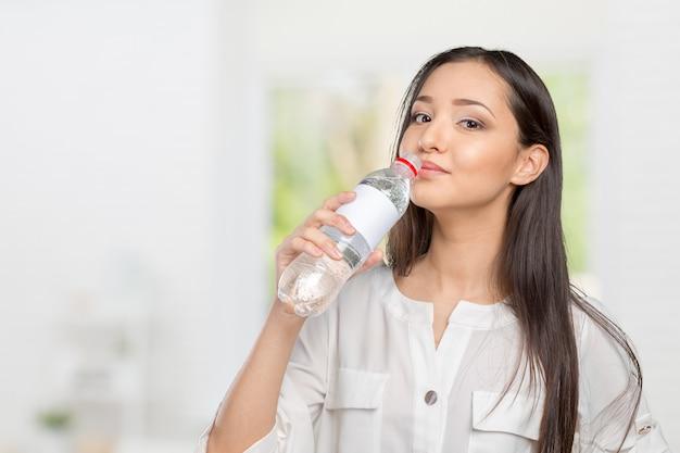 Jeune femme montrant une bouteille d'eau