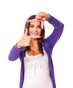Jeune femme montrant le cadre des doigts