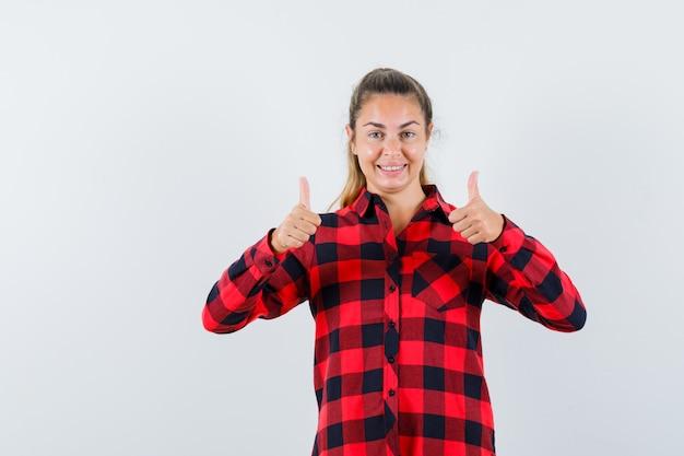 Jeune femme montrant deux pouces vers le haut en chemise à carreaux et à la joyeuse