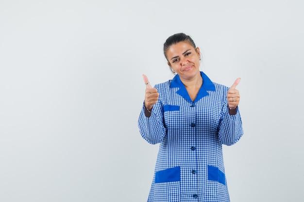 Jeune femme montrant deux pouces vers le haut en chemise de pyjama vichy bleu et à la jolie. vue de face.