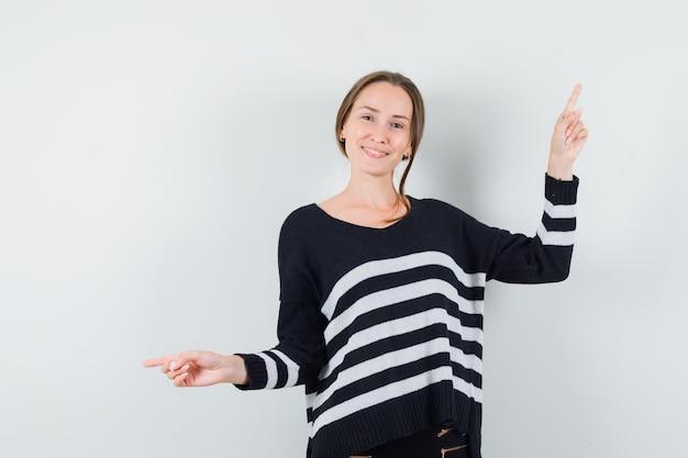 Jeune femme montrant des directions opposées avec l'index en maille rayée et pantalon noir et à heureux