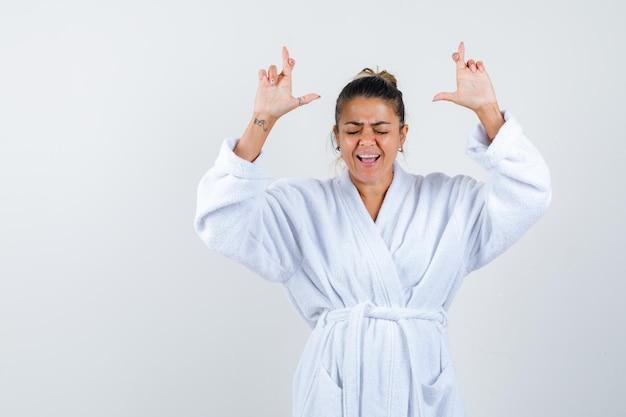 Jeune femme montrant les doigts croisés en peignoir