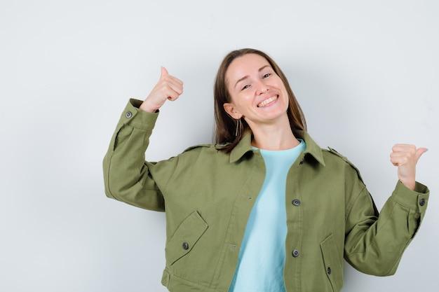 Jeune femme montrant un double coup de pouce en t-shirt, veste et à la gaieté. vue de face.