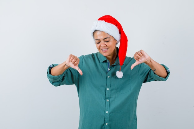 Jeune femme montrant double pouce vers le bas en chemise, bonnet de noel et à la gaieté, vue de face.