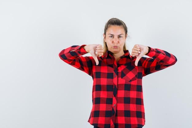 Jeune femme montrant le double pouce vers le bas en chemise à carreaux et à la vue pensive, de face.