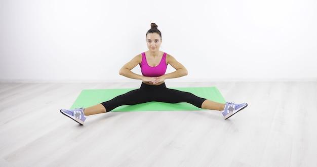 Jeune femme montrant des exercices médicaux dans la salle de gym beau corps mode de vie sain