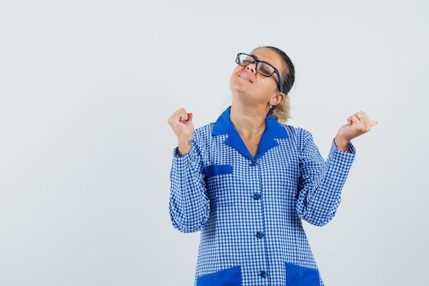 Jeune femme montrant le gagnant pose en chemise de pyjama vichy bleu et lunettes et à la jolie vue de face.