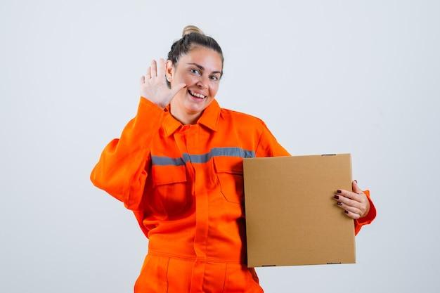 Jeune femme montrant le geste d'adieu tout en tenant la boîte en uniforme de travailleur et à la joie. vue de face.