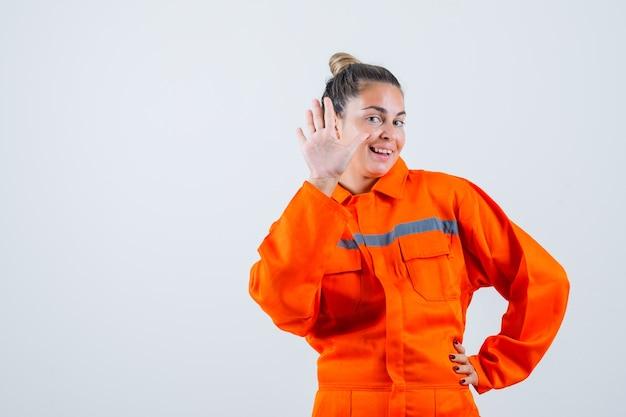 Jeune femme montrant un geste d'adieu en uniforme de travailleur et à la joie. vue de face.