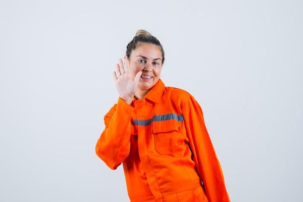 Jeune femme montrant le geste d'adieu en uniforme de travailleur et à la jolie vue de face.