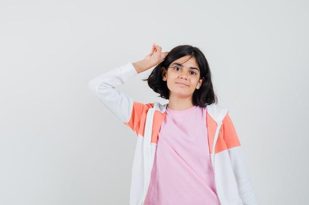 Jeune femme montrant un geste d'adieu en veste, chemise rose et à l'air heureux.