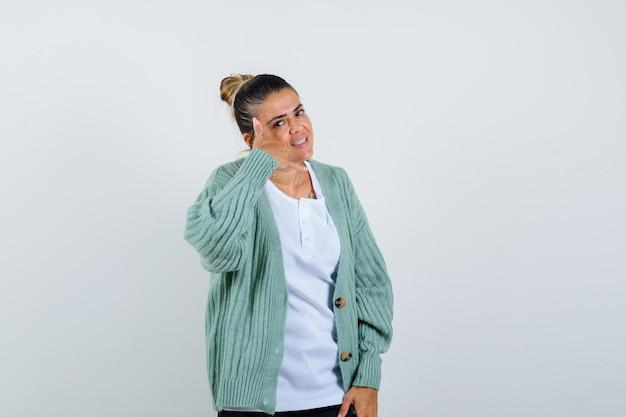 Jeune femme montrant le geste de l'appel en t-shirt, veste et ayant l'air confiant