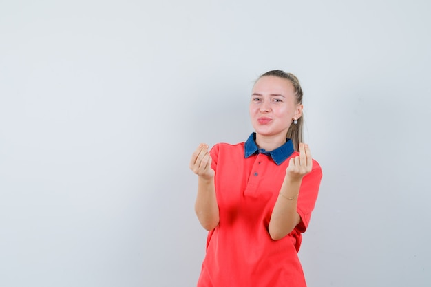 Jeune femme montrant le geste de l'argent en t-shirt et à la joie