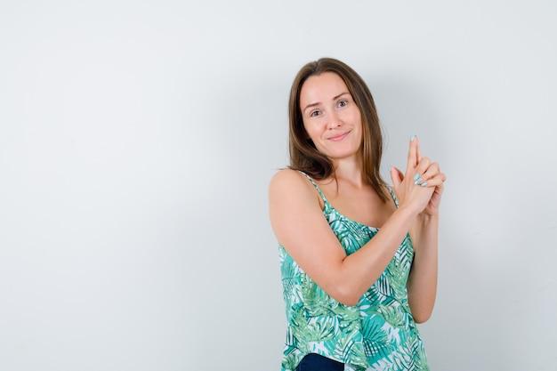 Jeune femme montrant un geste d'arme à feu et regardant joyeusement, vue de face.
