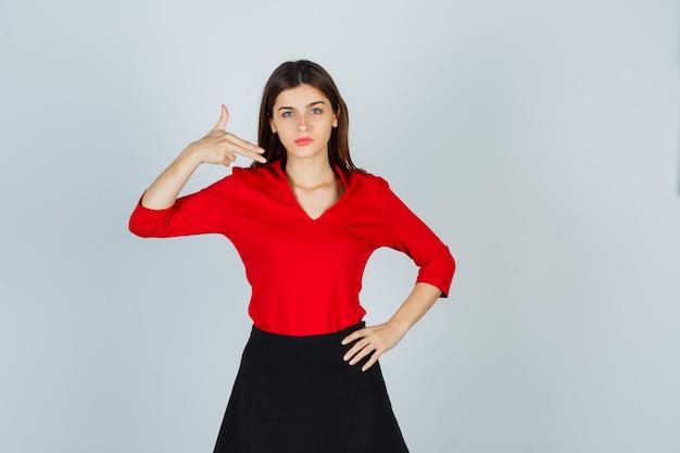 Jeune femme montrant le geste des armes à feu, tenant la main sur la hanche en chemisier rouge