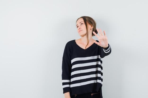 Jeune femme montrant le geste d'arrêt en chemise décontractée et à l'ennui