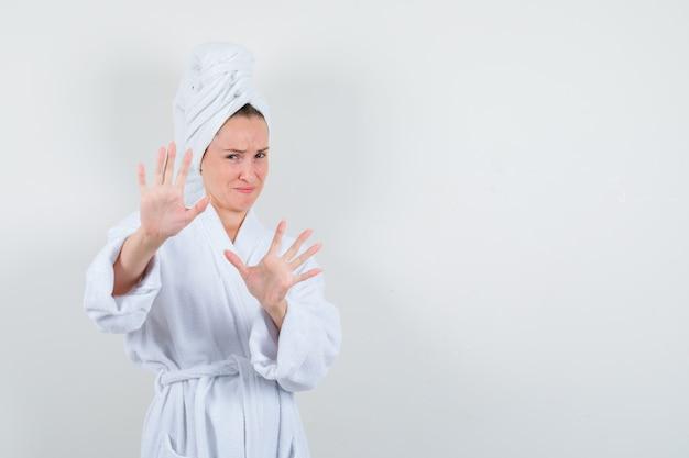 Jeune femme montrant le geste d'arrêt en peignoir blanc, serviette et à la dégoûté. vue de face.