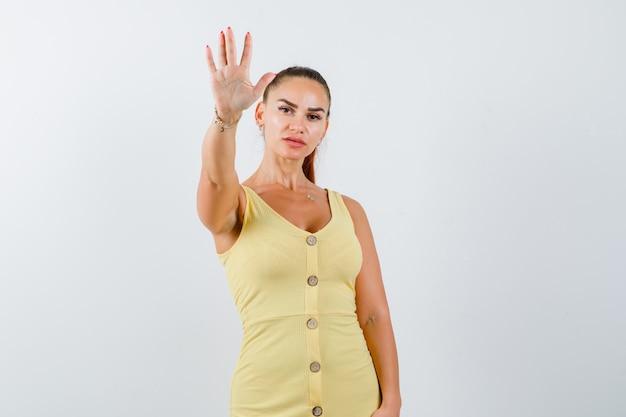 Jeune femme montrant le geste d'arrêt en robe jaune et l'air confiant. vue de face.