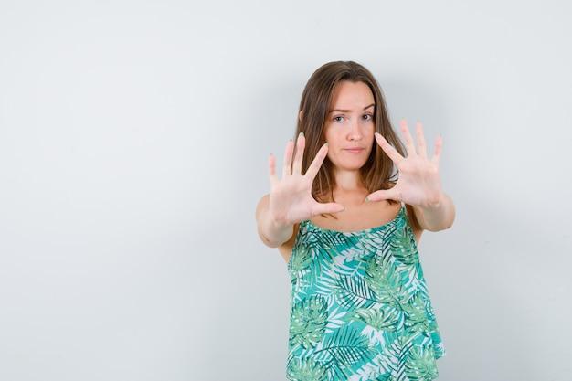 Jeune femme montrant un geste d'arrêt et semblant sérieuse, vue de face.