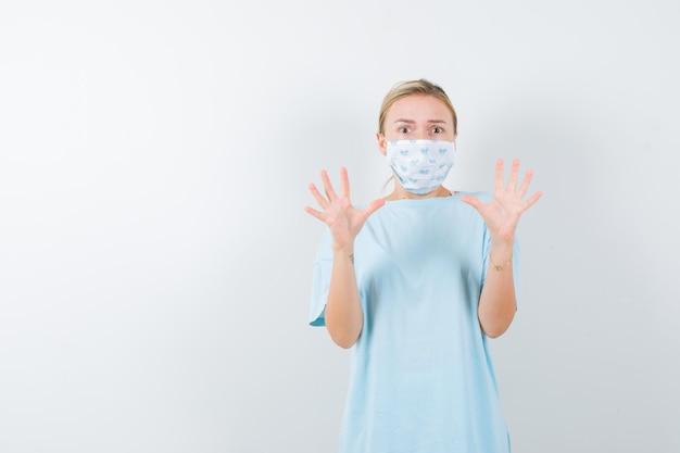 Jeune femme montrant un geste d'arrêt en t-shirt, masque et ayant l'air effrayée isolée