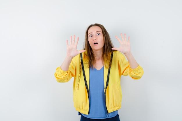Jeune femme montrant un geste d'arrêt en t-shirt, veste et ayant l'air effrayée. vue de face.