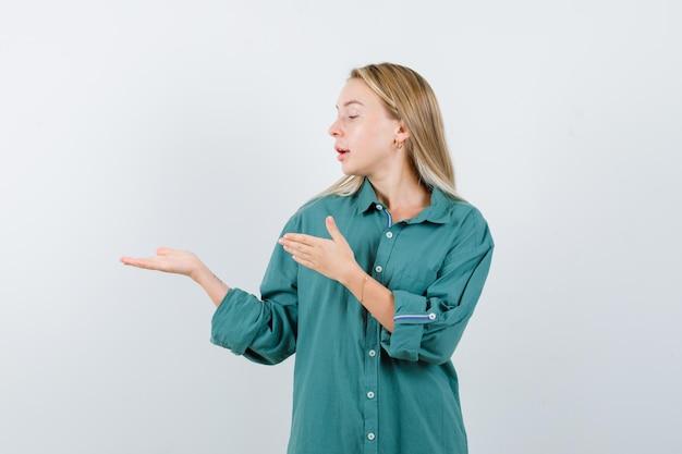 Jeune femme montrant un geste de bienvenue en chemise verte et semblant confiante