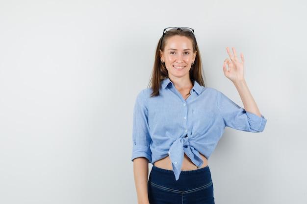 Jeune femme montrant un geste correct en chemise bleue, pantalon et à la satisfaction.