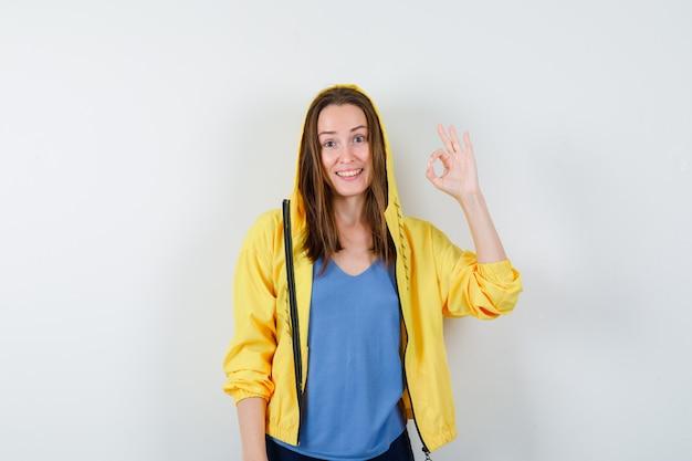 Jeune femme montrant un geste correct en t-shirt, veste et l'air confiant, vue de face.