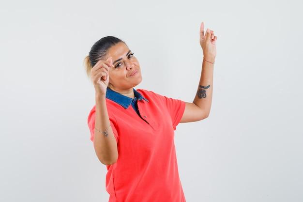Jeune femme montrant le geste de danse en t-shirt rouge et à la jolie. vue de face.
