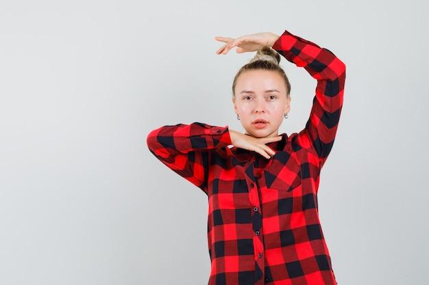 Jeune femme montrant le geste de danse traditionnelle en chemise à carreaux et à la belle