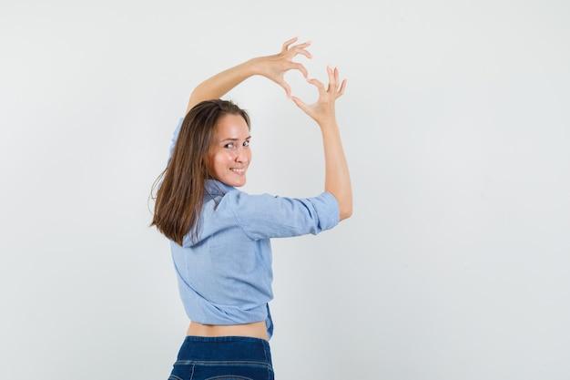 Jeune femme montrant le geste du cœur en regardant en arrière en chemise bleue, pantalon et à la joie