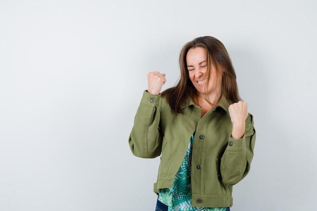 Jeune femme montrant le geste du gagnant en blouse, veste et semblant heureuse. vue de face.