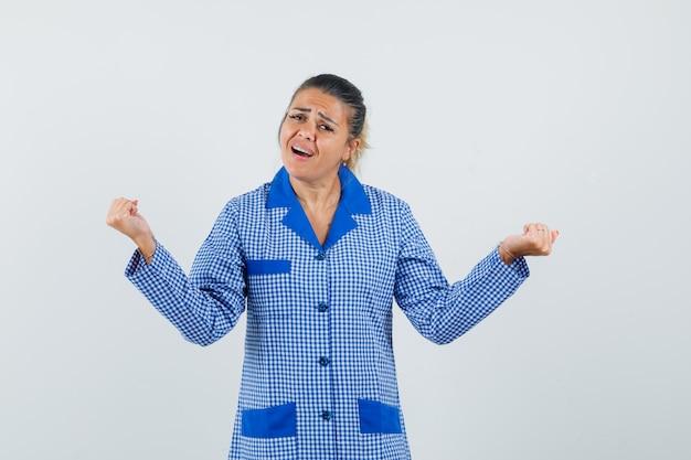 Jeune femme montrant le geste du gagnant en chemise de pyjama vichy bleu et à l'excitation. vue de face.